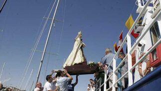Momento del embarque de la talla de la Virgen en una de las embarcaciones portuenses./Andrés Mora