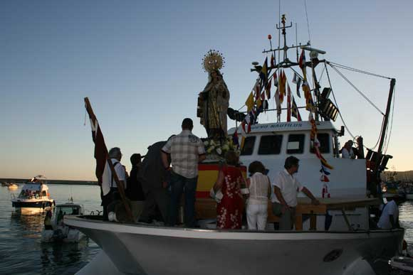 La virgen es transportada por un barco en el puerto de la ciudad./Jesús Marín