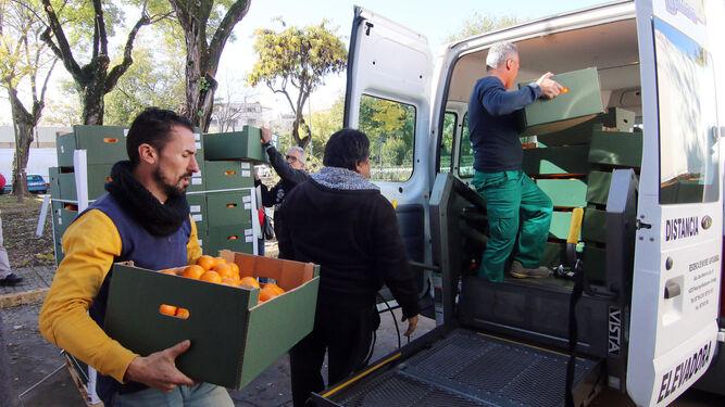 Un grupo de voluntarios carga una furgoneta con naranjas en el Banco de Alimentos.