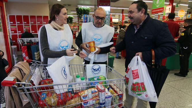 Marina Almenara y otro voluntario reciben una bolsa de alimentos de manos de un cliente en el Deza de la Ronda del Marrubial.