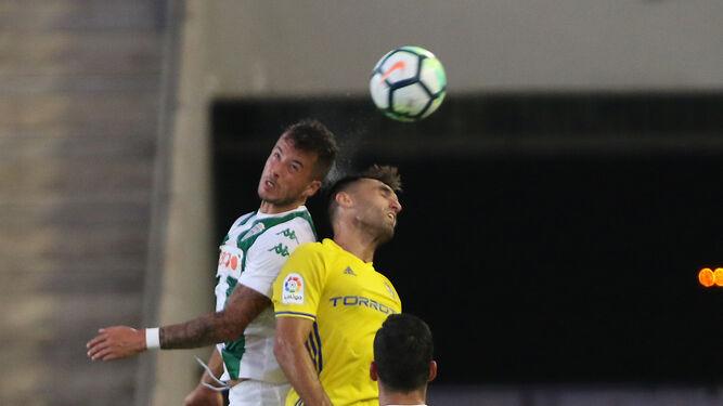 Pinillos pugna un balón aéreo con Barral ante la atenta mirada de Alfaro.