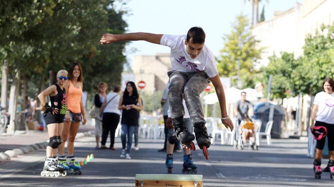 Un joven salta un obstáculo montado en unos patines.