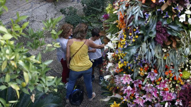 Una familia observa la intervención de Flores Cosmos, en el patio del Archivo Municipal.
