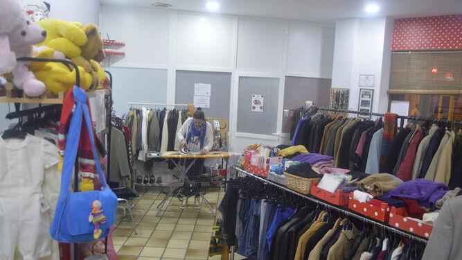 Una responsable de Sonrisa de Lunares plancha ropa en su tienda de la calle Compositor Ramón Medina.