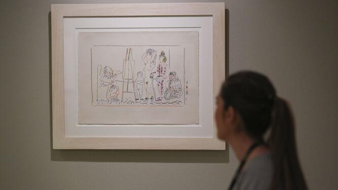 Una joven observa 'El taller del viejo pintor'.