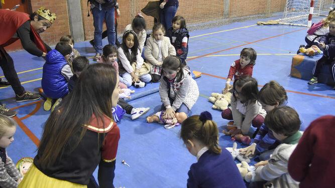 La doctora Noelia Muñoz, caracterizada como Blancanieves, enseña a los más pequeños la posición para practicar una RCP.