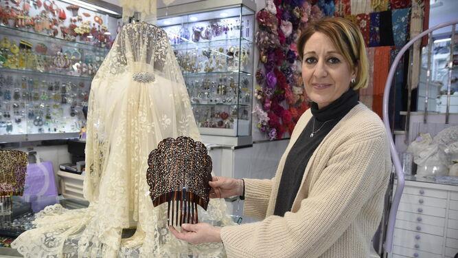 Una de las dependientas de la tienda Abril muestra una peina y una mantilla detrás.