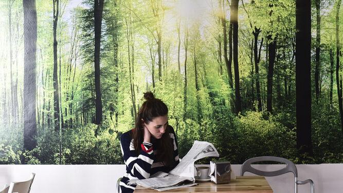 Una clienta lee el periódico mientras desayuna en el Café Pombo.