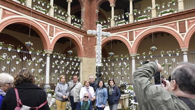 Varias personas se fotografían delante de la Cruz de la hermandad del Huerto.