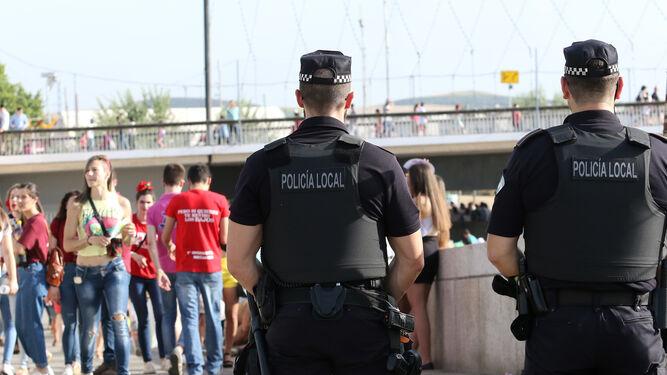 Dos agentes de la Policía Local realizan labores de seguridad en el botellón clásico de los miércoles de Feria.