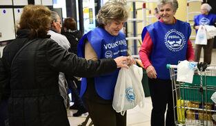 Una señora entrega una bolsa con alimentos a una de las voluntarias.