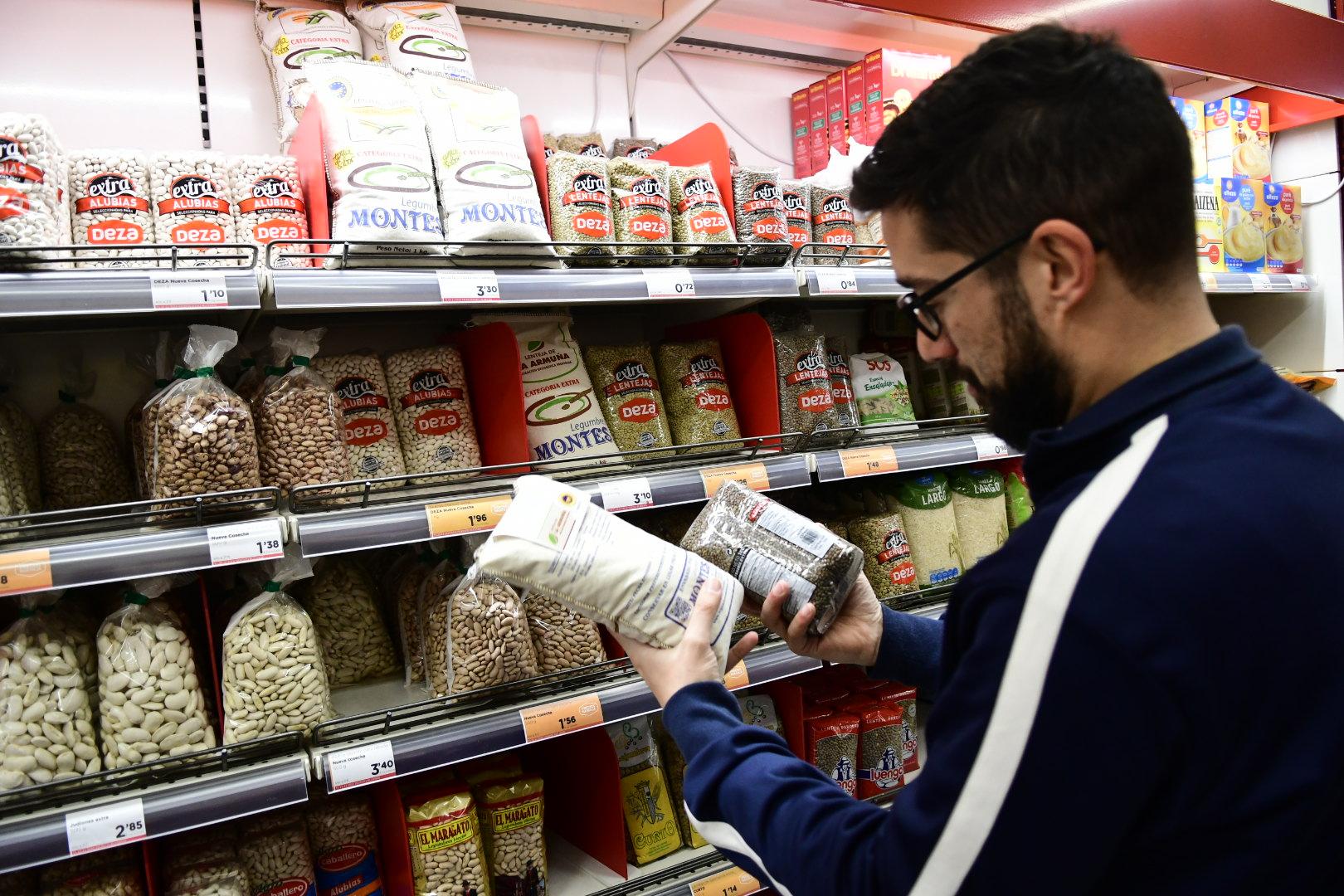 Un joven selecciona varios artículos para entregarlos al Banco de Alimentos.