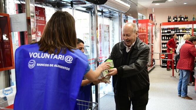 Un hombre entrega una caja de leche a unas voluntarias del Banco de Alimentos.