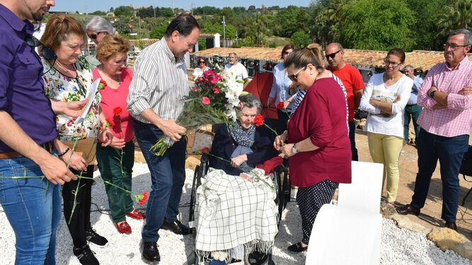 Una familia realiza una ofrenda floral