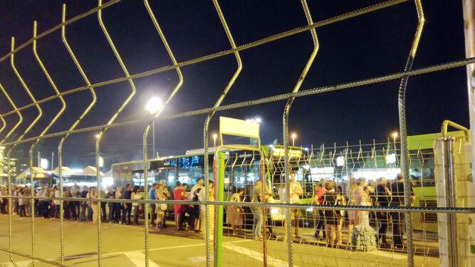 Varias personas esperan su turno para acceder a un autobús en la Feria