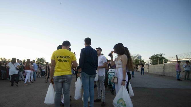Varios jóvenes cargan con botellas de alcohol para hacer botellón.