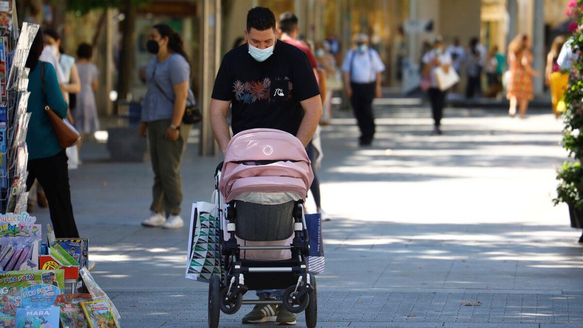 Un hombre pasea a un bebé en un cochecito.
